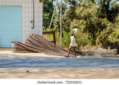 OUSSOUYE, SENEGAL - APR 30, 2017: Unidentified Senegalese little girl walks along the road with bag in Oussouye, a town in Senegal