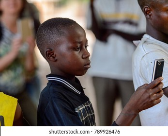 OUSSOUYE, SENEGAL - APR 30, 2017: Unidentified Senegalese  little boy holds a cellphone in the Sacred Forest near Kaguit village