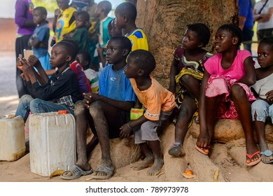 OUSSOUYE, SENEGAL - APR 30, 2017: Unidentified Senegalese little children sit around the tree in the Sacred Forest near Kaguit village