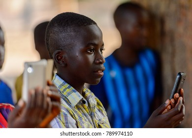 OUSSOUYE, SENEGAL - APR 30, 2017: Unidentified Senegalese little boy in plaid shirt looks ahead and holds a cellphone  in the Sacred Forest near Kaguit village