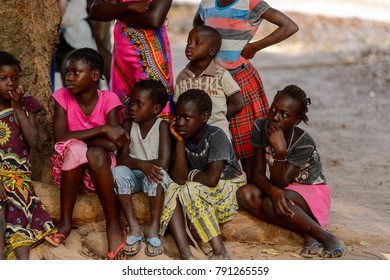 OUSSOUYE, SENEGAL - APR 30, 2017: Unidentified Senegalese little boys and girls sit around the street in the Sacred Forest near Kaguit village