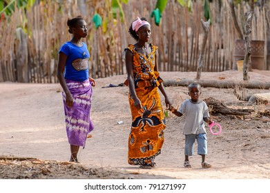 OUSSOUYE, SENEGAL - APR 30, 2017: Unidentified Senegalese two women in traditional clothes walk with a little boy in the Sacred Forest near Kaguit village