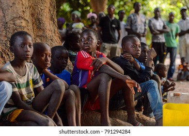 OUSSOUYE, SENEGAL - APR 30, 2017: Unidentified Senegalese little boys sit near the tree  in the Sacred Forest near Kaguit village
