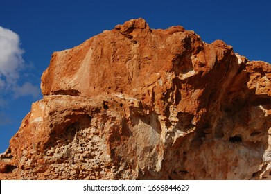 Out back Australian rocky cliff face, looking up to the top of the cliff, deep blue sky and small clouds.