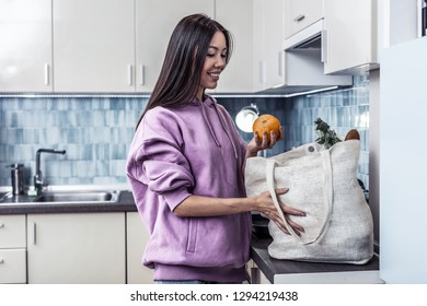 Out of bag. Dark-haired family woman wearing purple hoodie taking fruits and vegetables out of bag