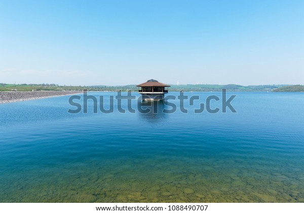Out in the calm, clear, rippled water of Carsington Reservoir, in Derbyshire, is a wood and concrete water control tower.