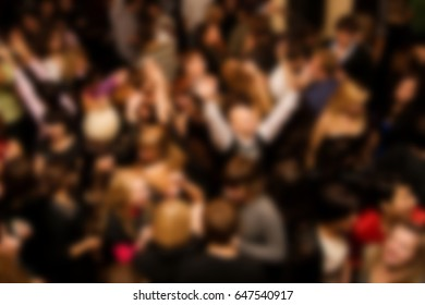 Out of focus background with dancing crowd of people in nightclub.Young adult audience have fun in the club.Electronic music festival event,entertainment show.Party poster back ground
