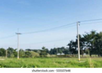 Out of focus background of grassland with utility poles and power lines-grass field
