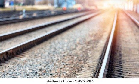 Out of focus blurred railway going straight ahead to sunny evening horizon with sun flares background with copy space.