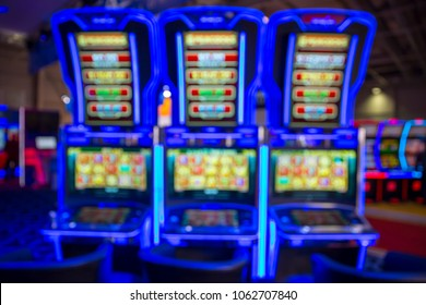 Out of focus blurry image of casino equipment. Blurred slot machines in a casino. Illuminated in blue.