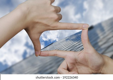 out of focus business building and fingers creating a square making the vision clear