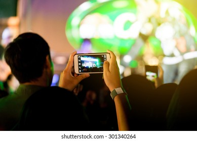 Out of focus crowd of Audience enjoying music in concert on stage use smart phones take photo.