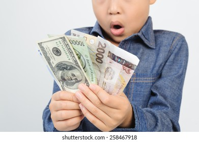 Out focus face Young boy excite with american and korean bank note in his hand