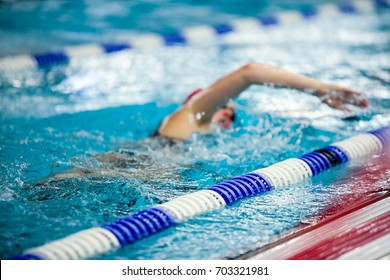 Out of focus female swimmer crawling. Anonymous athlete in a pool, motion blur.