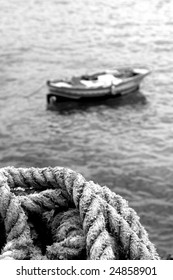 Out of focus fisherman boat with a close up rope.