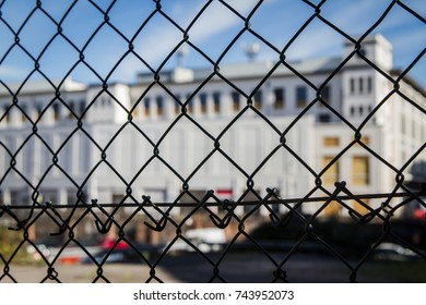 Out of focus historical building behind a wire fence