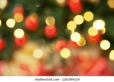 Out of focus holiday bokeh background. Christmas presents under the tree, close-up.