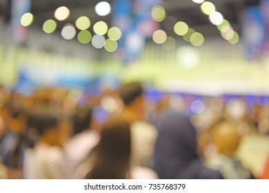 out of focus image of people watching a show on stage - blurred background concept
