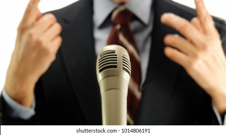 out of focus man speaking in front of microphone