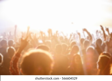 Out of focus music festival background.Crowded dance floor in nightclub.Group of people have fun on concert.Big live musical show in the club.Fans wave hand to favorite singer on stage