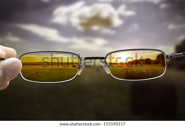 out of focus nature at sunset with hand holding a glasses that correct the vision