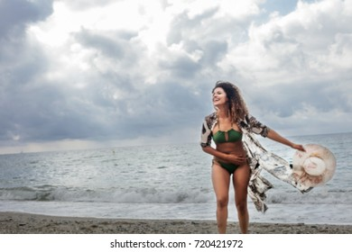 Out of focus portrait of gorgeous woman feeling free on the beach