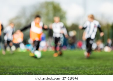Out of focus shot of young children playing soccer on green soccer pitch.
