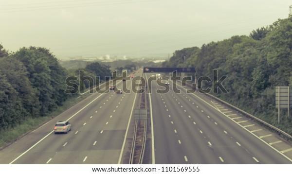 Out of focus slow traffic on M5 Motorway B, Captured in Clapton-in-Gordano, England - split toning
