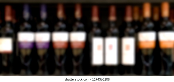 Out of focus supermarkt shelves with bottles of red wine.