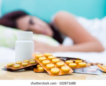 Out of focus woman resting in bed with some pills from her medical treatment on a table in the foreground