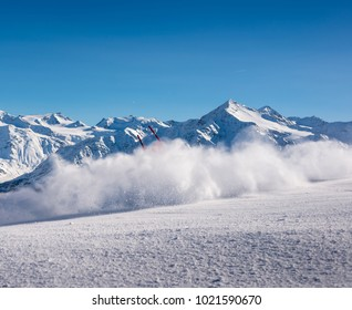 Out of frame skiier with flying snow powder at a downhill ski course in the Italian Alps with stunning mountainscape background, Bormio, Italy