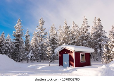 An out house surrounded by snow clad trees