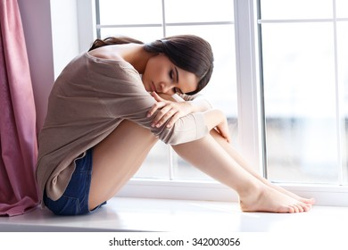 Out of mood. Pleasant gloomy attractive girl sitting on the window sill and leaning on her legs while thinking out