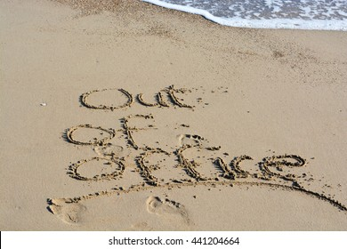 Out of office text written in sand on a beach suggesting work life balance