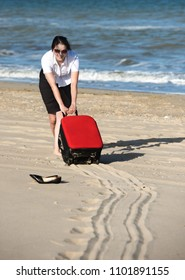 Out of office – vacation at sea. Woman drags the suitcase over the sands to the seaside.