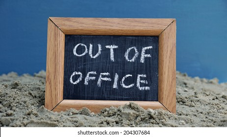 Out of office written on a chalkboard at the beach