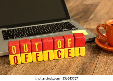 Out of Office written on a wooden cube in a office desk