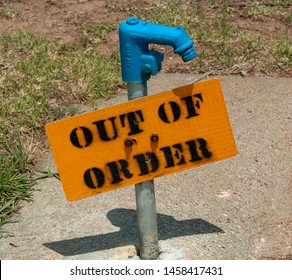 Out of Order, black text on yellow sign, water spigot.