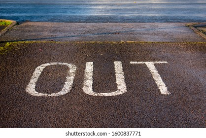 'Out' painted on road surface in a car park