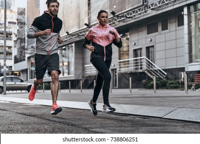 Out for a run. Full length of young couple in sport clothing running through the city street together
