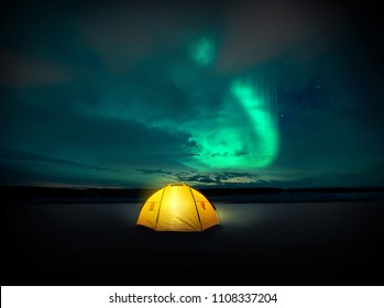 Out in the wilderness The Norther lights ( Aurora Borealis) dances across the night sky in Sweden, above the glowing lights from the camping tent. Photo Composite.