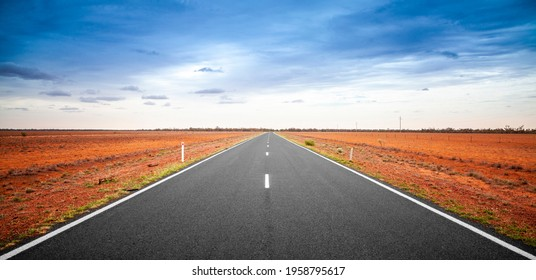 Outback Queensland road in Australia with a stormy sky. An empty open road stretching to the horizon. Single lane sealed highway with deep orange red soil on both sides. Travel adventure.