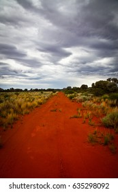 Outback road in Australia with a stormy sky. Portrait, red dirt road