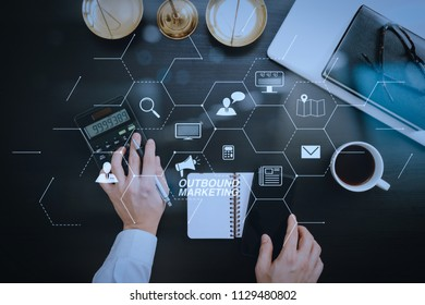 Outbound marketing business virtual dashboard with Offline or interruption marketing.justice and law concept.businessman or lawyer or accountant working on accounts using a calculator.