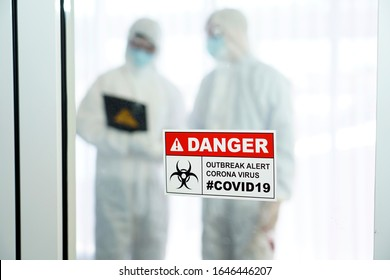 Outbreak alert Coronavirus COVID 19, COVID 19 signage in front of control area with doctors in personal protective equipment inside.