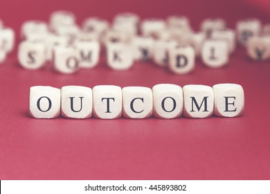Outcome word written on wood cube with red background