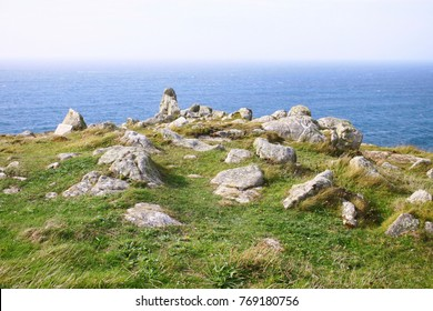 Outcrop of rocks on grass, next to the ocean on sunny but hazy day. Land's End, England.