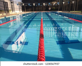 An outdoor 25 m. 4 lanes swimming pool in the morning after sunrise with reflection in the water