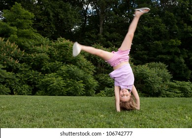 Outdoor action shot of a little girl in pink doing a cartwheel with motion in her legs
