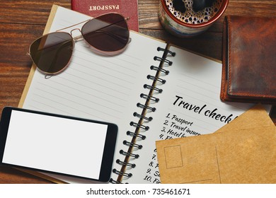 Outdoor activities accessories prepared for vacations journey and travel checklist in the notepad. Also a smartphone with place for text on blank screen and a cup of coffee for traveler. Top view.